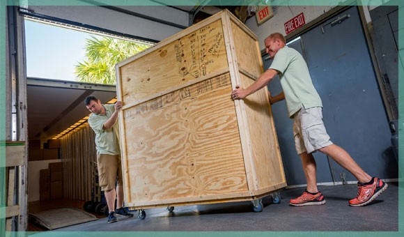 White Glove Movers moving large crate into moving truck | William C. Huff Companies - Moving & Storage