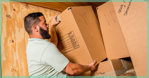 taking packed box out of moving truck and into new family house | William C. Huff Companies - Moving & Storage